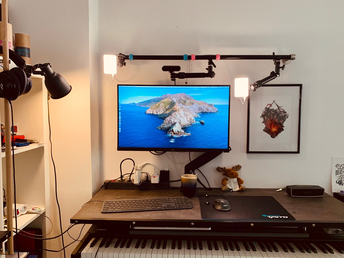 A desk with a monitor, mouse and keyboard. Above the monitor: a wall mounted bar holding a webcam and two lights on articulated arms